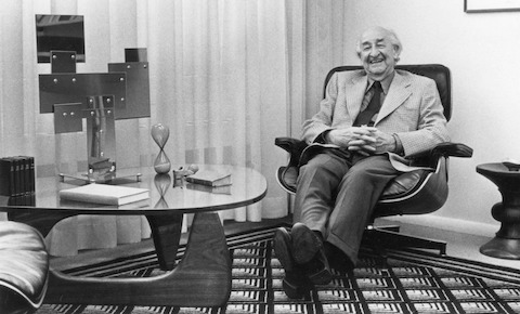Herman Miller founder D.J. De Pree reclines in an Eames Lounge Chair next to a glass-top Noguchi Table.