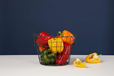 A black wire basket containing colorful peppers.
