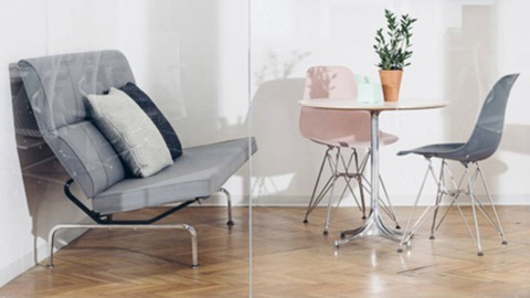 A Haven Setting at Harry's Grooming Headquarters with an Eames Sofa and pink and grey Eames Shell chairs. Select to play a case study video on collaboration.