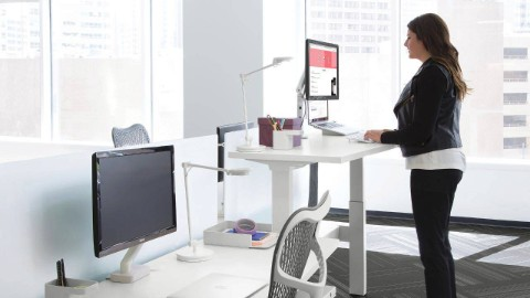 A woman views a computer monitor while standing at an adjustable-height desk.