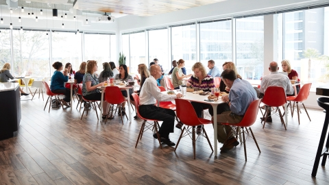 People eat lunch in the Plaza at Tavistock Development Company. The space is outfitted with red Eames Shell chairs. Select to play a case study video.