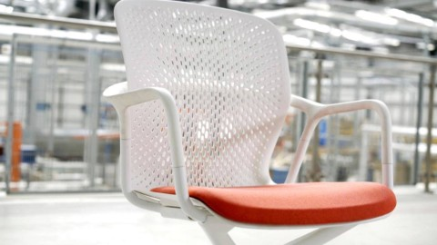 A white Keyn side chair with a red upholstered seat. Select to play a video about the design of Keyn.