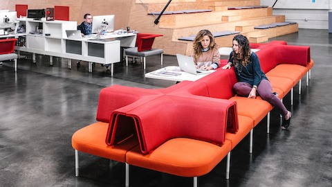 Two women sit on red Public Office Landscape settees and chat while looking at a laptop. Select to play a video of the fuseproject case study.