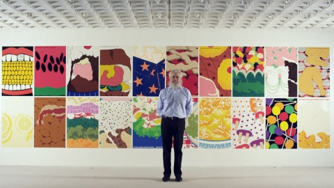 Graphic designer Steve Frykholm stands before a wall of posters. Select to play a video about Herman Miller's picnic posters.