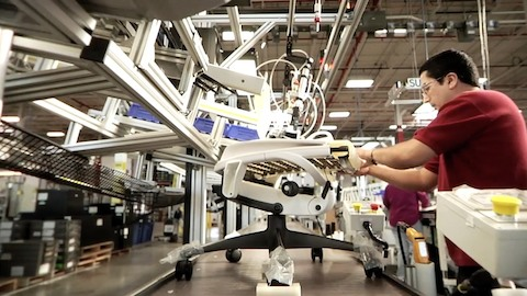 A worker inspects the upholstery of an Embody ergonomic desk chair on the assembly line. Select to play a video about our manufacturing process.