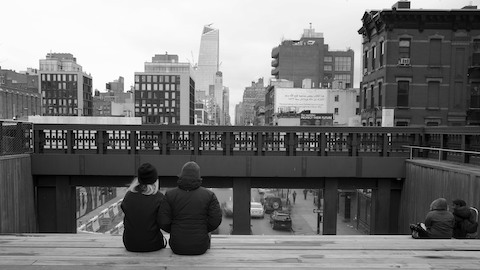 Two people sitting on a bridge and overlooking a cityscape. Select to play a video about George Nelson's book How To See.