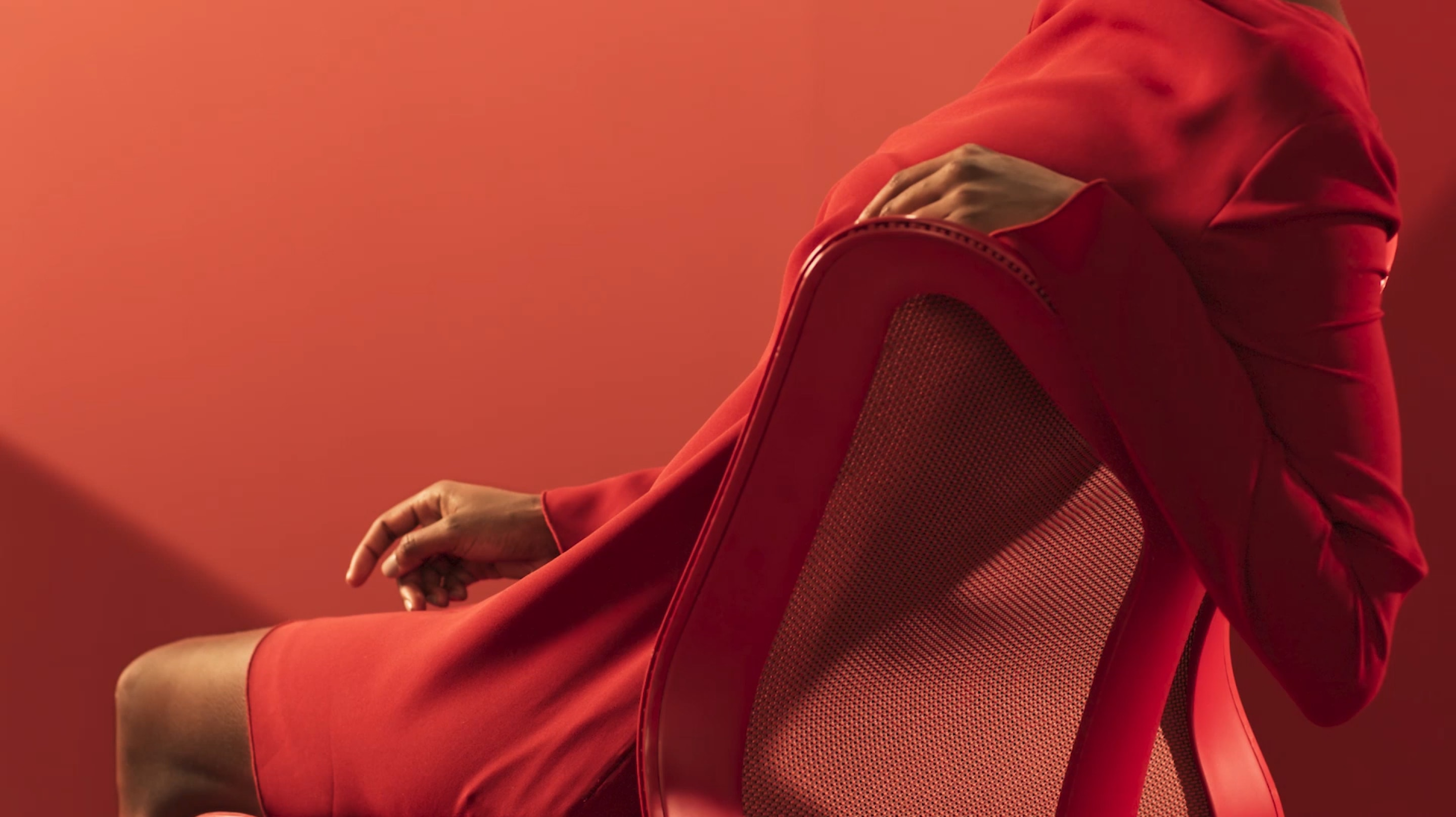 A woman in a red dress reclines with her arm over the backrest of a Canyon red Cosm Chair. Select play button to start video.