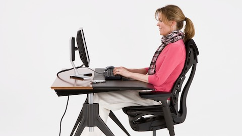 Profile view of a woman keying at an Envelop adjustable desk. Select to view a video about Envelop.