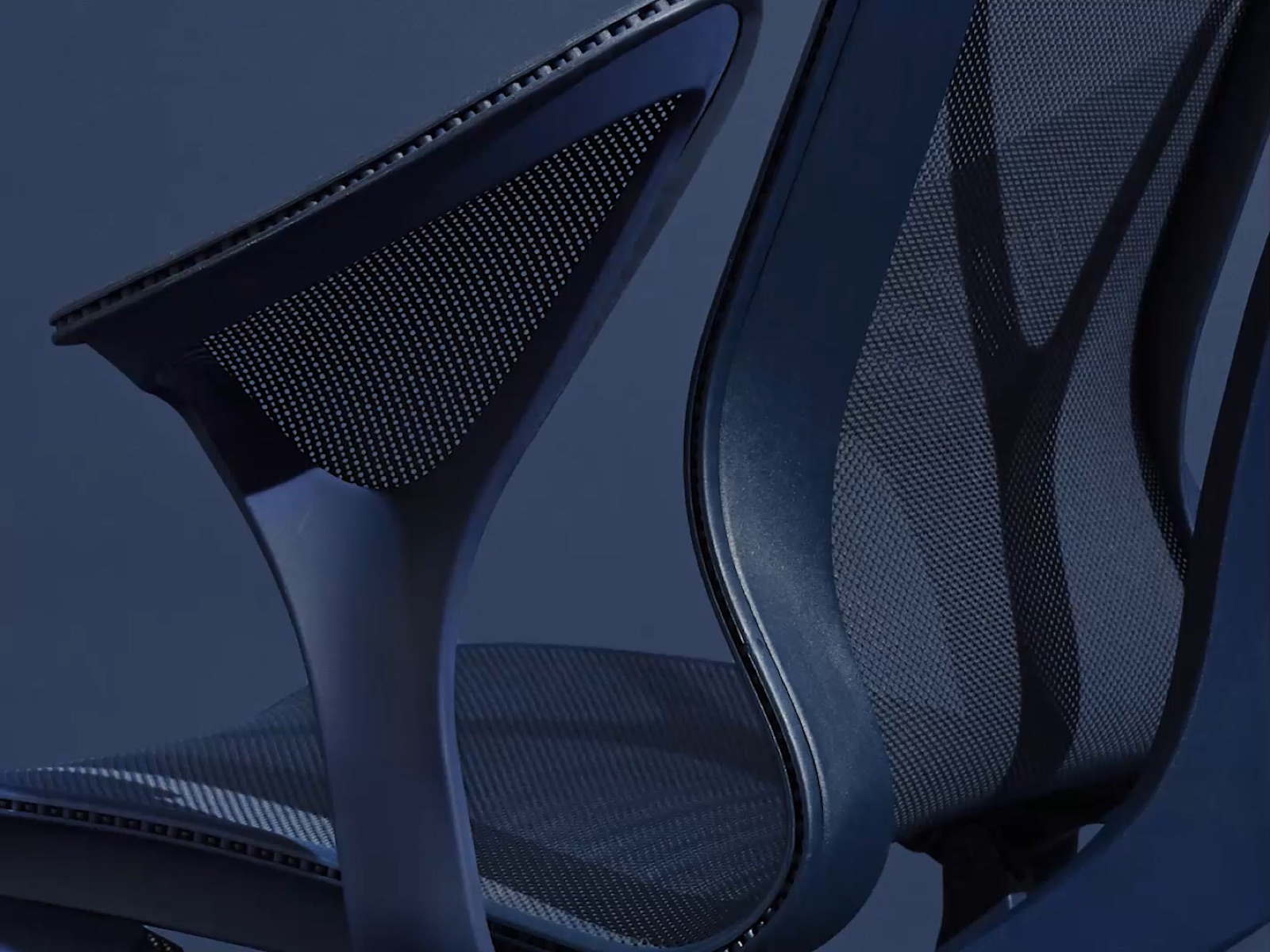 A close-up from behind of the leaf arm on a Nightfall dark blue Cosm ergonomic chair.