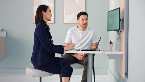 A physician and patient sitting around an Intent table and wall unit reviewing results on a monitor screen. Select to play a video on how Intent keeps the focus on the conversation.