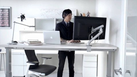 A man works on a computer while standing at a height-adjustable desk. Select to view a video about Renew Sit-to-Stand Tables.