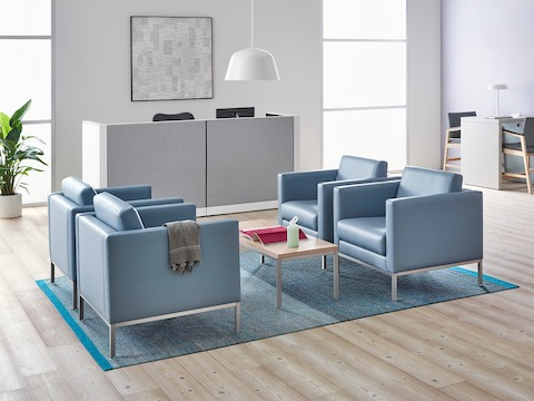 A healthcare reception area featuring four light blue lounge chairs.