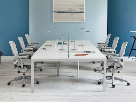 A white rectangular meeting table with three light grey Aeron office chairs on either side.