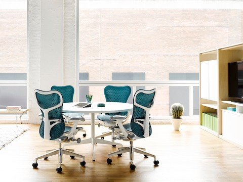 Four Blue Mirra 2 Office Chairs Surround A White Eames Table With Round Top In