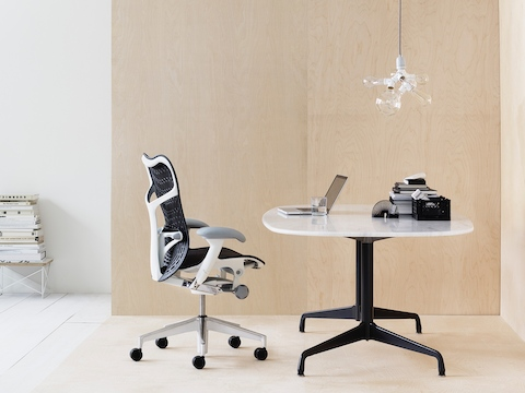 A black Mirra 2 office chair paired with an Eames Table with a white top and black base.