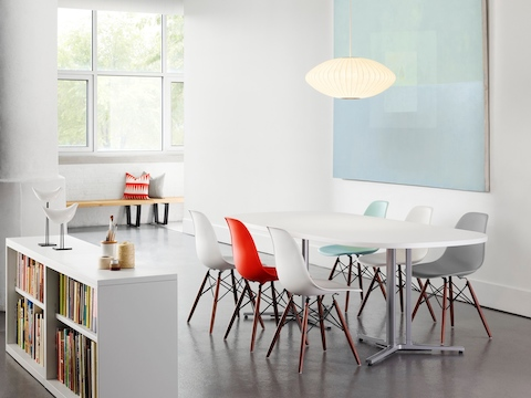An open meeting area featuring an oval Everywhere Table and Eames Molded Plastic Chairs in various colours.