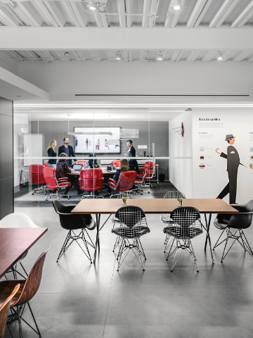 Colleagues gather in a glass-walled meeting room adjacent to an interaction space featuring a Nelson X-Leg Table and Eames Wire Chairs.