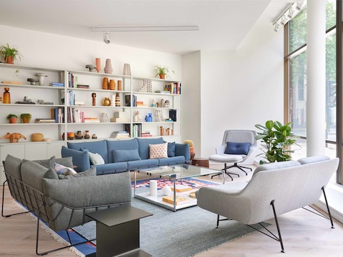 Collection of sofas, a lounge chair and side tables in front of a large bookcase.