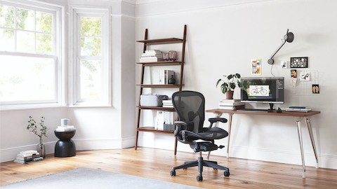 A residential workpoint featuring an Airia Desk, black Aeron office chair, and Polygon Wire Table. Select to shop the Herman Miller store and other online retailers.