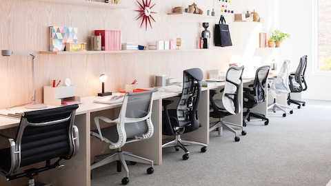 Six different models of Herman Miller office chairs pushed under a long desk. Select to find links to Herman Miller authorized retailers.