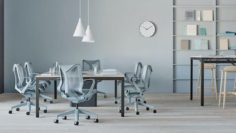 Locale elements divide space in a collaboration area that includes light grey Aeron office chairs and Wireframe lounge chairs. Select to search for a Herman Miller dealer.